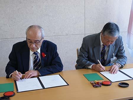 協定書にサインする土屋順敬理事長(左)と小林徹(右)