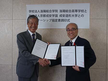 協定書を持って握手する土屋順敬理事長(右)と小林徹(左)